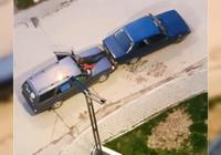 Otomobilin kaputuna oturup, ayaklarıyla öndeki aracı itti