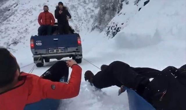 Karda kamyonete bağladıkları leğenle kaydılar